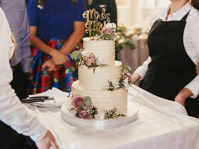 Modern wedding cake at wedding reception. Waiters taking out stylish white wedding cake with floral decor and mr mrs topper at wedding feast in restaurant. Luxury catering