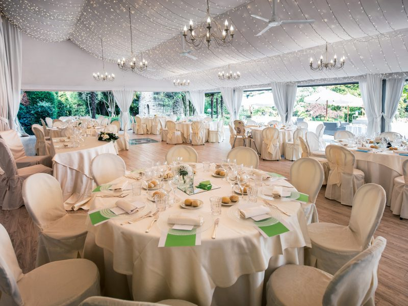 Wedding reception venue in a large marquis with elegant formal white table settings and a view of a garden